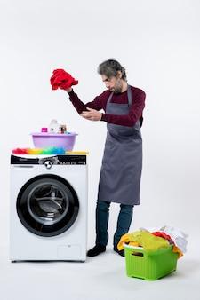 흰색 배경에 세탁기 근처에 서 있는 세탁물을 들고 있는 전면 보기 가정부 남자