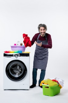 흰색 격리 된 배경에 세탁기 근처에 서있는 세탁물을 들고 전면보기 가정부 남자