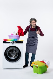 Front view housekeeper man holding red towel making thumb up sign laundry basket on white background