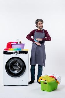 흰색 격리 된 배경에 세탁기 근처에 서있는 스폰지를 들고 전면보기 가정부 남자