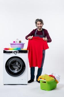 白い背景の上の洗濯機の近くに立っているtシャツを保持している正面図の家政婦の男