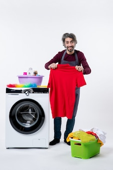 Front view housekeeper man holding t-shirt standing near washing machine on white background