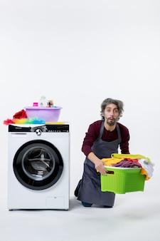Uomo della governante di vista frontale che si inginocchia vicino alla lavatrice che tiene cesto della biancheria su sfondo bianco