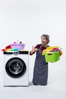Uomo della governante vista frontale che si inginocchia vicino alla lavatrice che punta al cesto della biancheria su sfondo bianco
