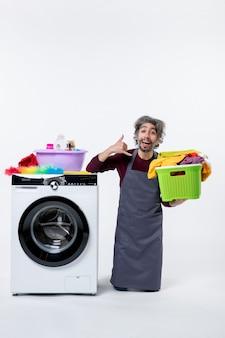 흰색 배경에 세탁 바구니를 들고 전화 표지판을 만드는 전면 보기 가정부 남자