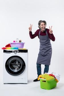 Uomo della governante vista frontale che fa il segno della vittoria in piedi vicino al cesto della biancheria della lavatrice su sfondo bianco