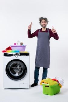 흰색 배경에 세탁기 세탁 바구니 근처에 서서 손가락으로 가리키는 전면 보기 가정부 남자