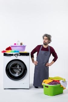 白い背景の上の洗濯機の近くにひざまずいて腰に手を置く正面図の家政婦の男