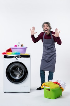 Вид спереди экономка мужчина поднимает руки, стоя возле корзины для белья стиральной машины на белом фоне