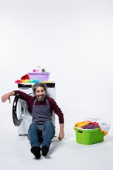 白い孤立した背景の上の洗濯かごの近くに座っている正面図の家政婦の男