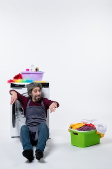 Front view housekeeper man sitting near laundry basket reclining washer on white background