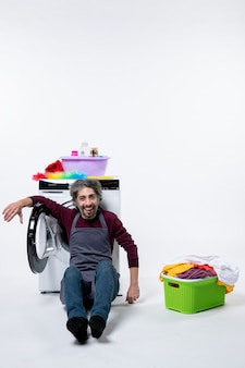 Front view housekeeper man sitting near laundry basket on white isolated background