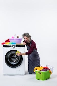 Uomo della governante vista frontale in piedi sul ginocchio vicino alla lavatrice su sfondo bianco