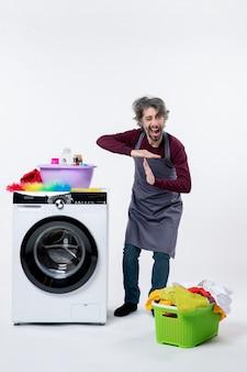 Uomo della governante vista frontale in piedi vicino al cesto della biancheria della lavatrice bianca sul pavimento