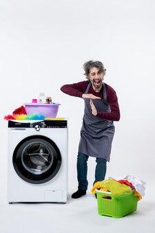 Вид спереди экономка, стоящая возле белой корзины для белья стиральной машины на полу