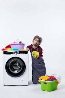 흰색 배경에 세탁물을 들고 무릎에 서 있는 전면 보기 가정부 남자