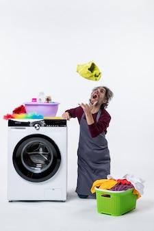흰색 배경에 공중에 세탁물을 던지고 무릎에 서있는 전면보기 가정부 남자