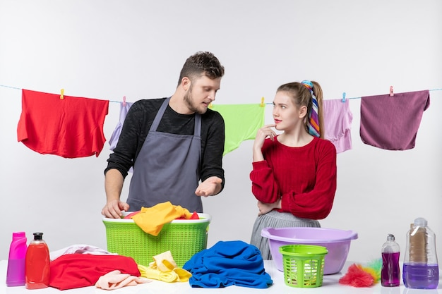 Front view of housekeeping day man and wife standing behind table laundry baskets and washing stuffs on table clothes on rope