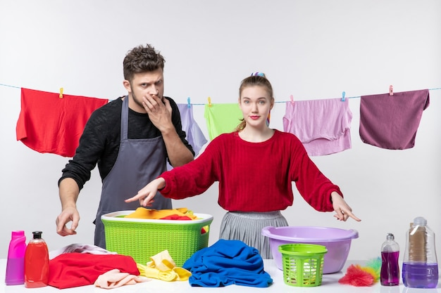 Front view of housekeeping husband and his wife pointing at detergents laundry basket and cleaning stuffs on table on white wall