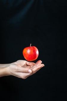 Вид спереди человеческая рука с яблоком на темноте