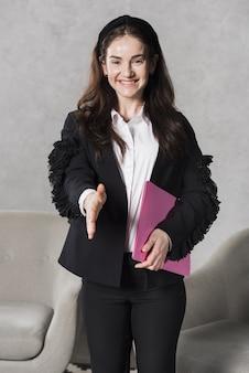 Vista frontale della donna delle risorse umane che dà scossa della mano prima dell'intervista