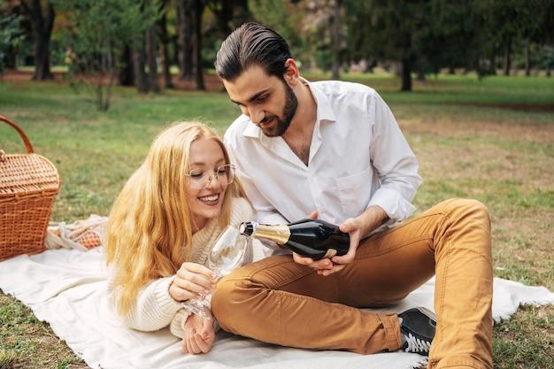 一緒にピクニックをしている正面図の夫と妻