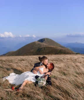 Front view of husband hugs his red-haired wife and kisses sitting on the grass