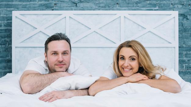 Vista frontale del marito e della moglie che si trovano sul letto bianco che guarda l'obbiettivo