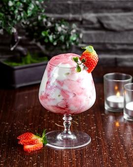 Gelato di vista frontale con marmellata di fragole in un bicchiere e fette di fragola