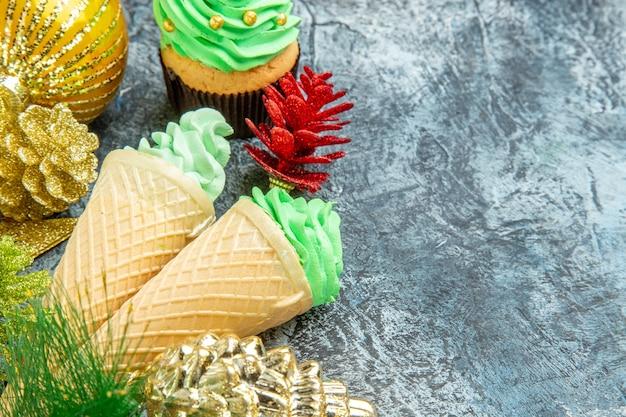 Vista frontale gelati albero di natale cupcake ornamenti di natale su grigio con posto libero
