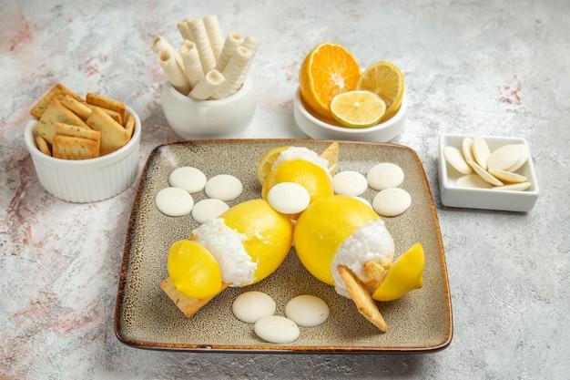 白いテーブルジュースカクテルフルーツドリンクにキャンディーとクッキーと正面のアイスレモン