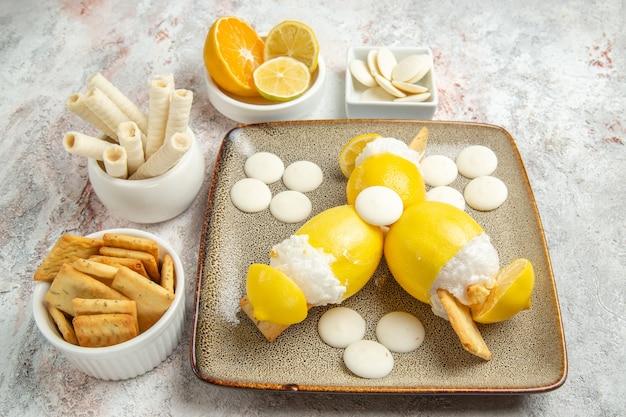 白いテーブルジュースカクテルフルーツにキャンディーとクッキーと正面のアイスレモン