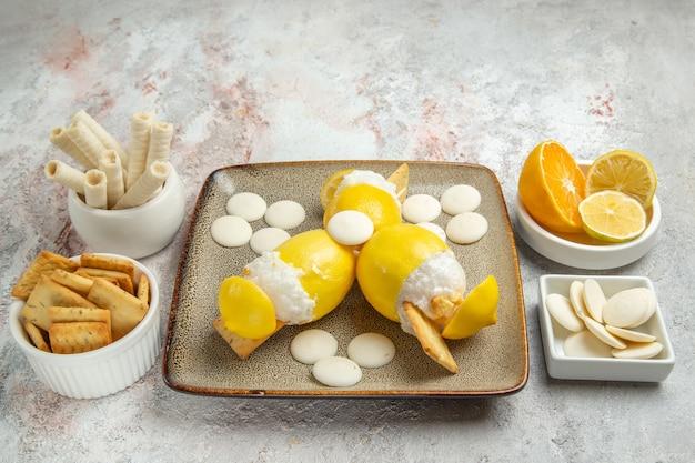 白いテーブルジュースカクテルフルーツドリンクにキャンディーとクッキーと正面図アイスレモン