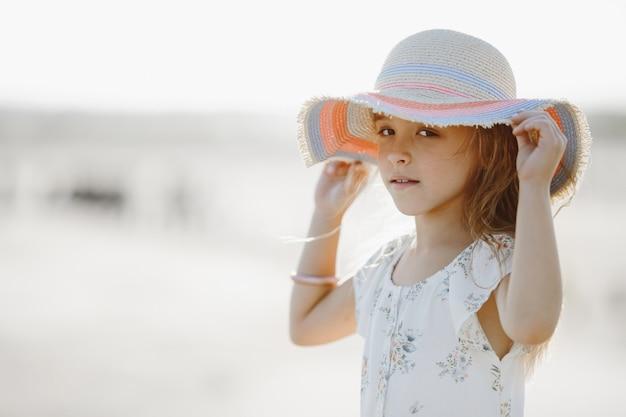夏のドレスの正面図はまっすぐ見て帽子の端を保持しています。