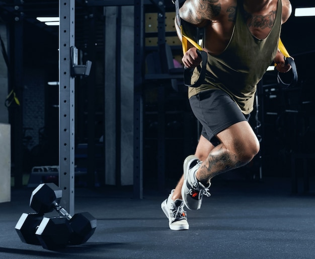 Front view of incognito bodybuilder running in place using ropes, dumbbells on floor.