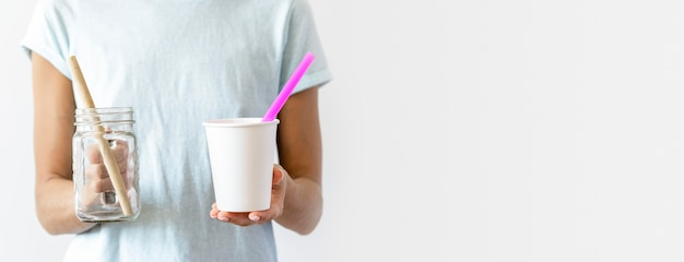 Front view individual holding plastic cups with copy space