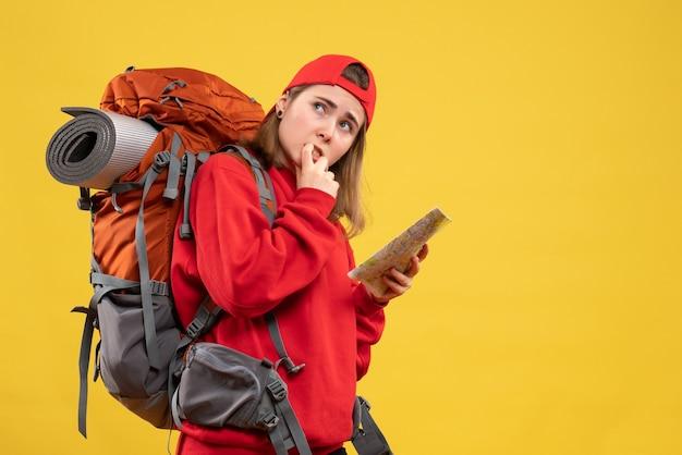 旅行マップを保持している正面図に興味のある女性のバックパッカー