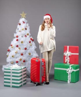 Вид спереди заинтересованная девушка в шляпе санта-клауса, стоящая возле белой рождественской елки