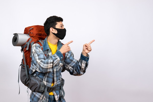 Front view interested male traveler with backpack and mask pointing at something