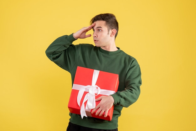 Front view interested man with green sweater standing on yellow