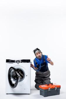 헤드 램프가 흰색 공간에 세탁기에 청진기를 놓는 전면 보기 관심 있는 수리공
