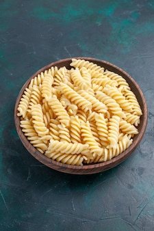 Front view italian pasta delicious looking inside brown pot on the dark-blue desk
