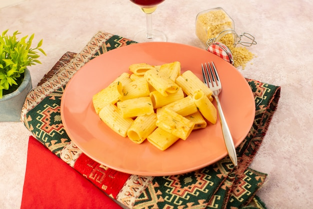 A front view italian pasta tasty meal inside pink plate along with raw pasta and glass of wine on colorful carpet and pink