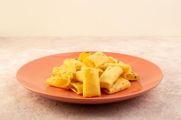 Un pasto gustoso della pasta italiana di vista frontale con le erbe verdi secche all'interno della zolla dentellare sul colore rosa
