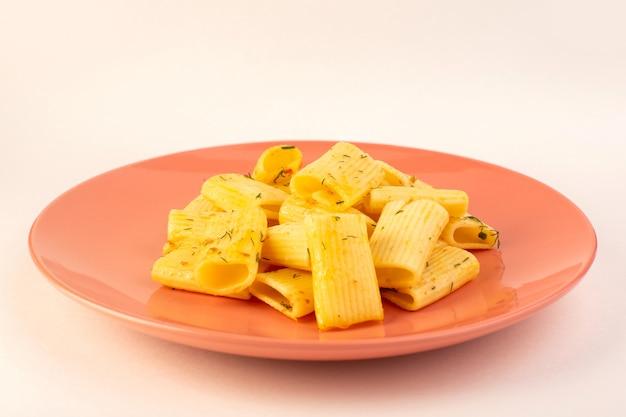 Una pasta italiana di vista frontale con erbe verdi secche all'interno del piatto rosa su bianco