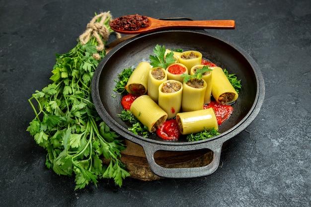 회색 공간에 팬 내부 녹색 토마토 소스와 고기 전면보기 이탈리아 파스타
