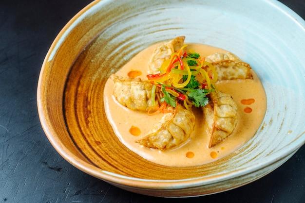 Вид спереди японские жареные пельмени гедзы в соусе с зеленью в тарелке