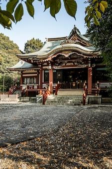 Vista frontale del tempio giapponese con foglie d'autunno