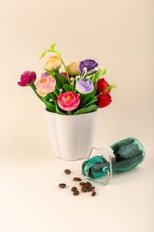 A front view jar with coffee and flowers on the pink table coffee color flower seed