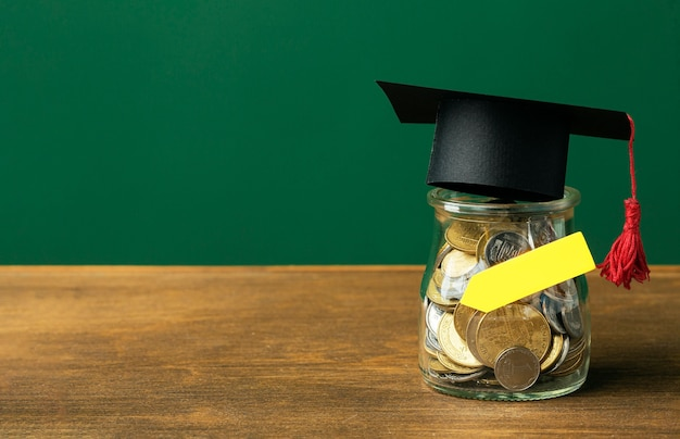 Front view of jar with coins and academic cap